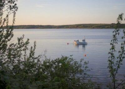 Blick vom Campingplatz: Fischerboot bei der Arbeit